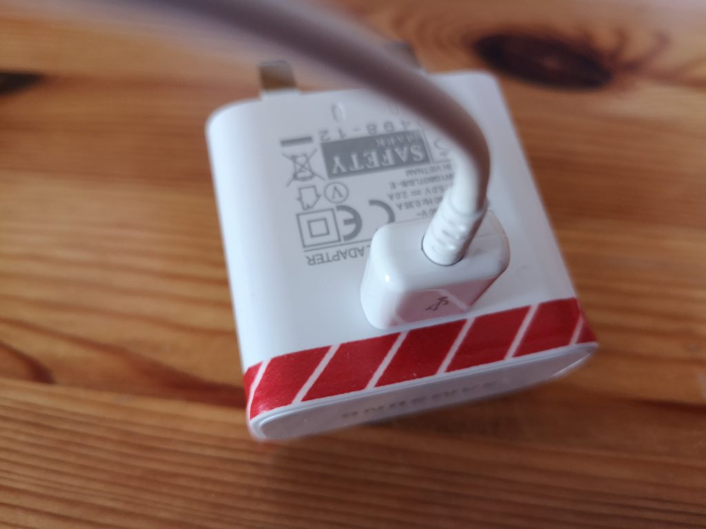 A tablet charger with striped washi tape wrapped around it