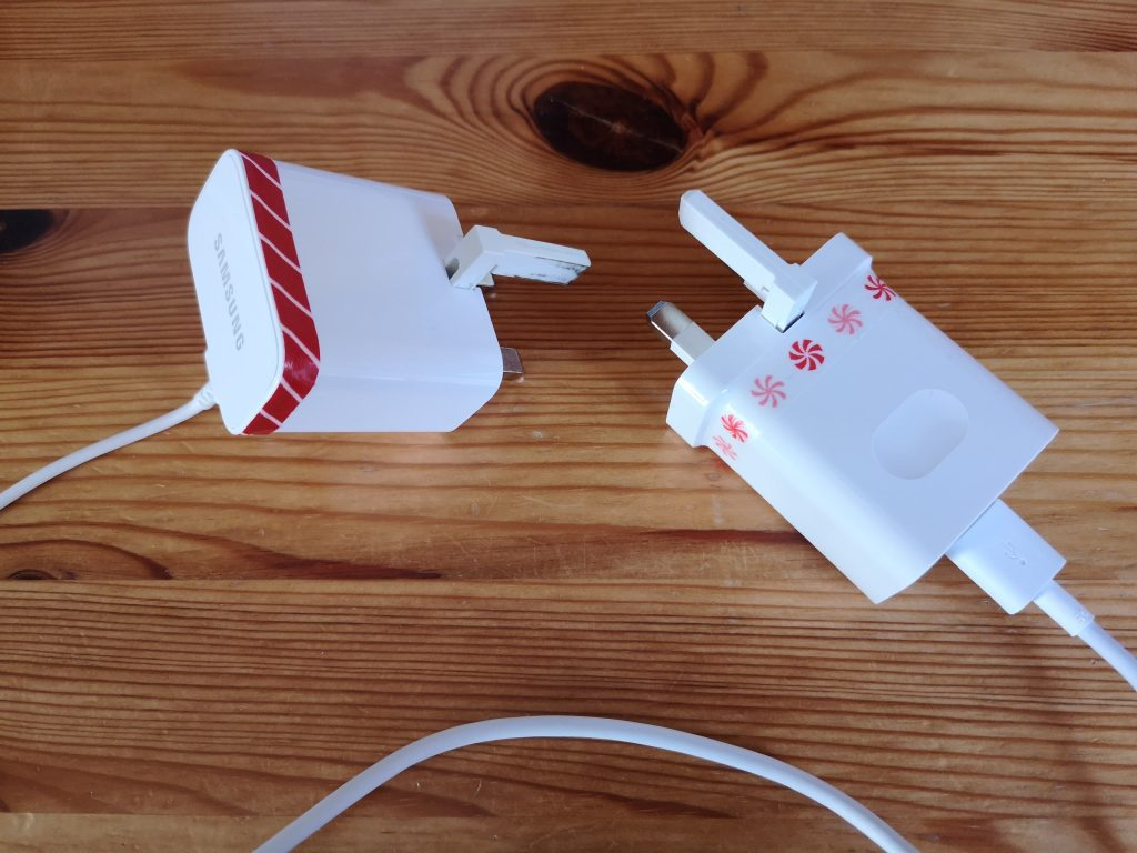Two white chargers that have thin strips of washi tape wrapped round them, in two different patterns.