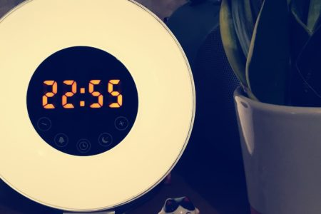 An alarm clock reading 22:55 on a bedside table. There is a plant in a white pot and a small cat ornament next to it.