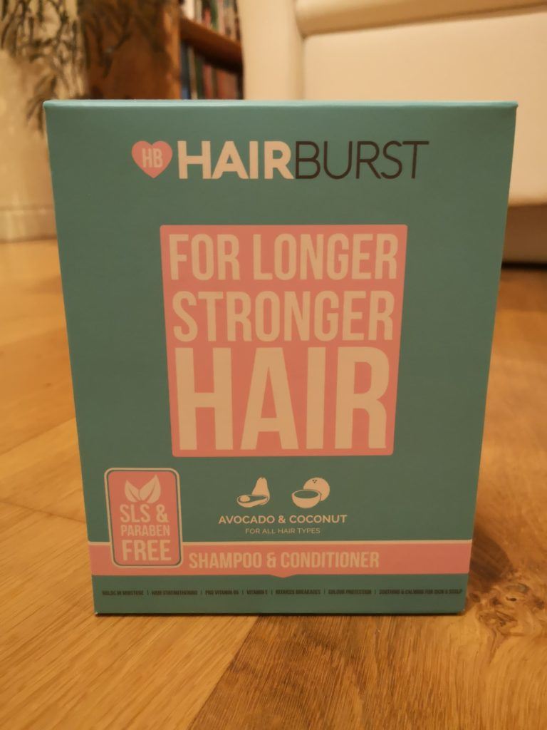 Hairburst Shampoo and Conditioner box, standing on a wooden floor.