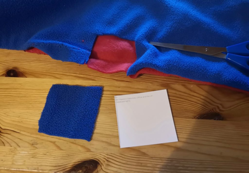 Cutting a square of blue fabric out of an old scarf.