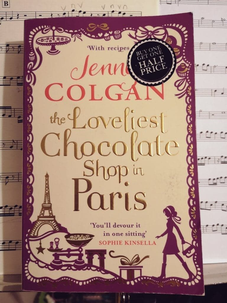 A paperback copy of The Loveliest Chocolate Shop in Paris by Jenny Colgan