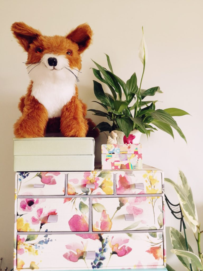 A stuffed toy fox next to a peace lily plant, on a set of mini drawers with a flower pattern on.