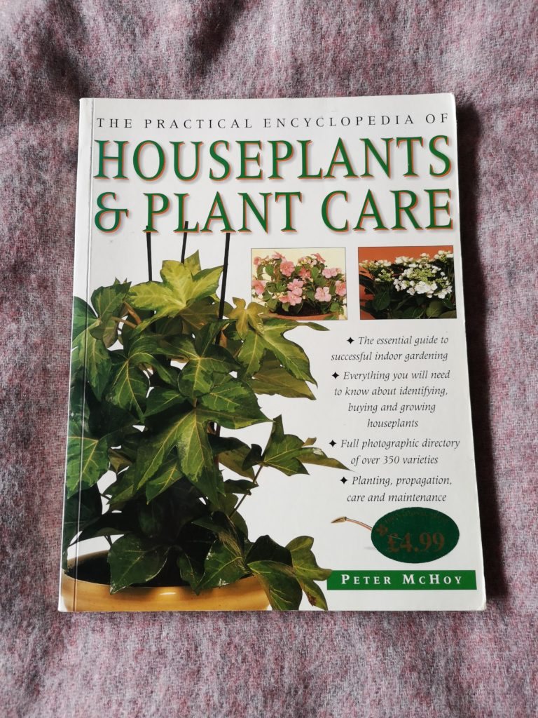 A copy of The Practical Encyclopedia of Houseplants & Plant Care, laying on a pink background