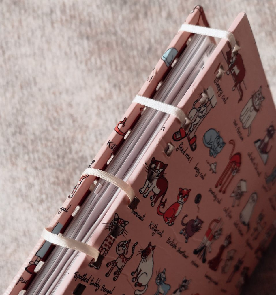 A pink notebook with a cat pattern on it, bound by pieces of cream ribbon