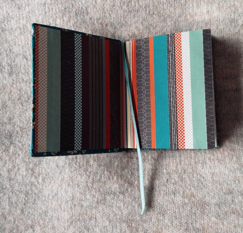 An open diary with a turquoise ribbon being used as a bookmark