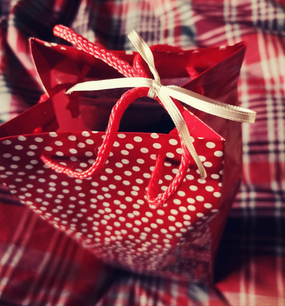 A red gift bag with the handles tied by a gold ribbon in a bow.