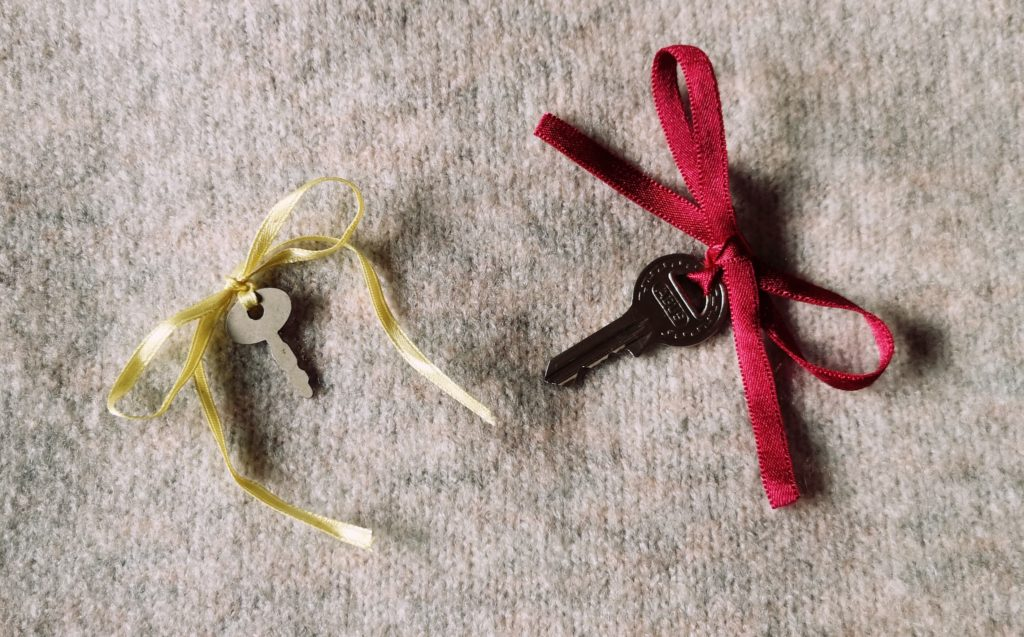 Two small keys, with a red and yellow ribbon tied to them in a bow