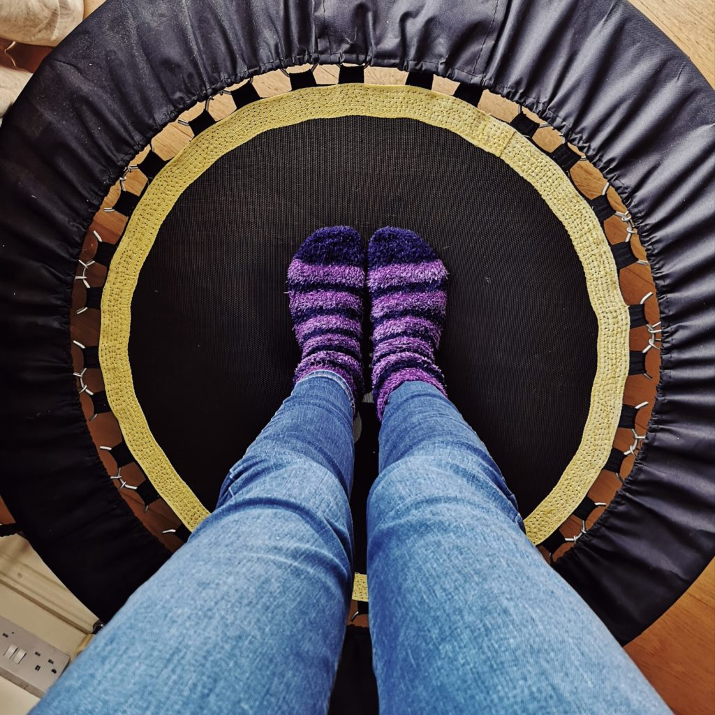 A pair of legs wearing blue jeans and stripy purple socks, standing on a trampette