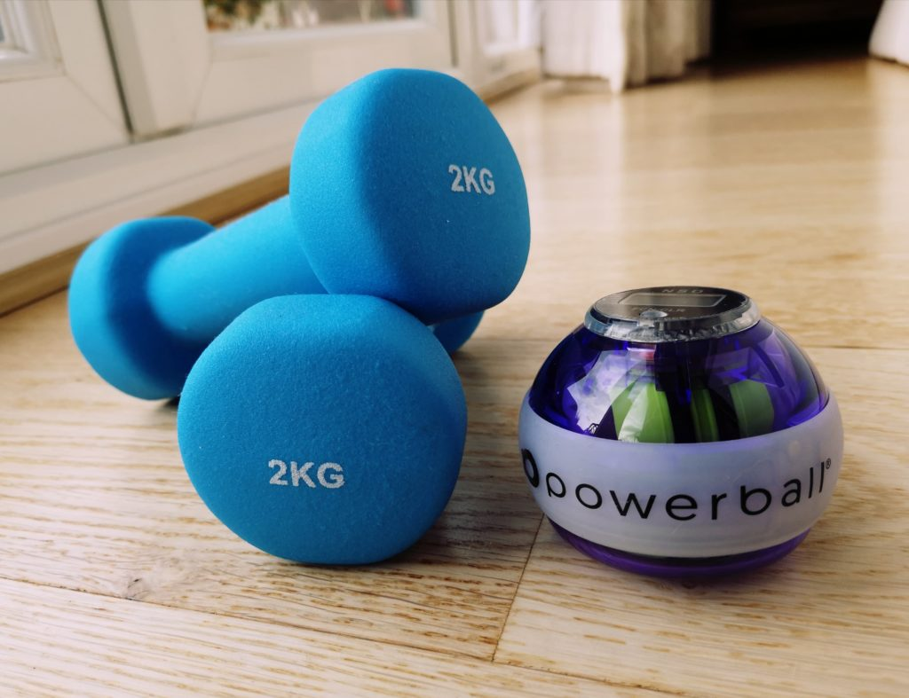a pair of blue 2kg weights and a purple and white powerball on a wooden floor