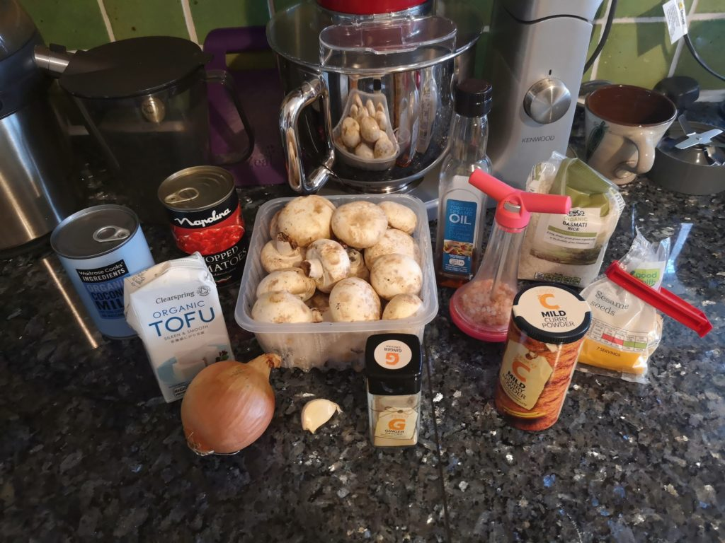 The ingredients for Mushroom and Tofu Mild Curry, laid out on a kitchen surface