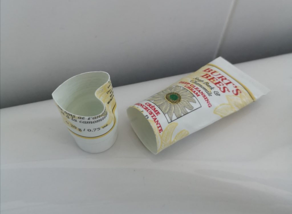 An empty tube of Burt's Bees - Soap Bark & Chamomile Deep Cleansing Cream, cut in half