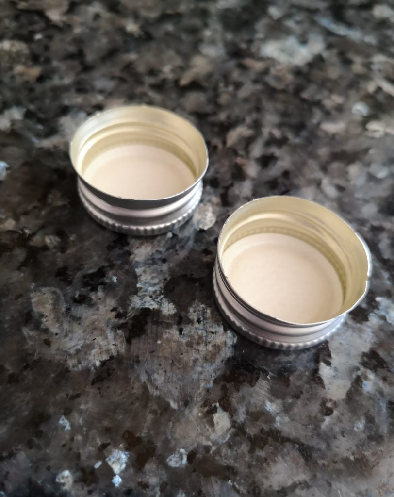 Two metal bottle lids.