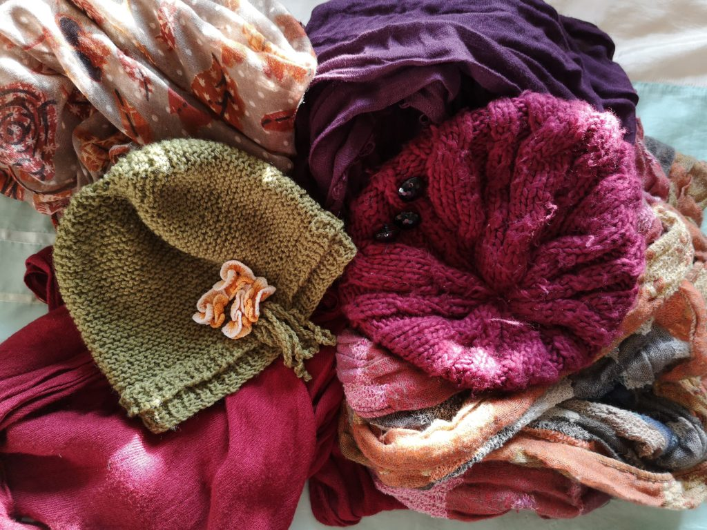 Autumnal scarves and hats laid out on my bed