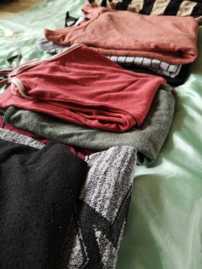 Several piles of tops in Autumnal colours, laid out on a bed.
