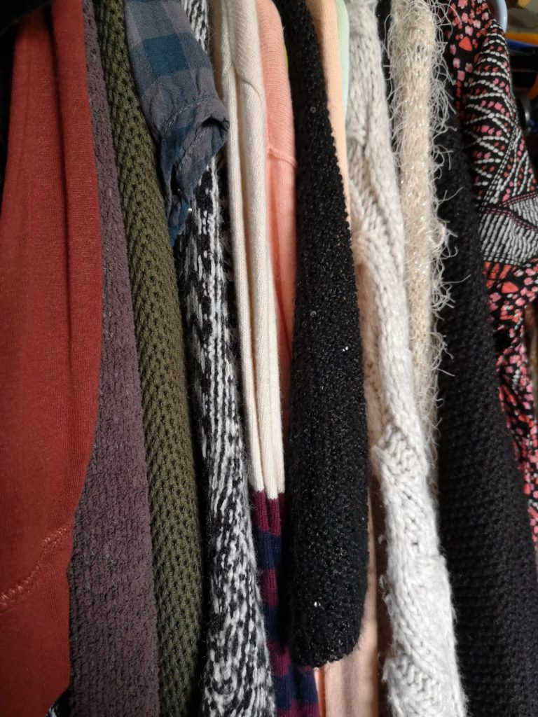 Various clothes in Autumnal colours, hanging in a wardrobe.