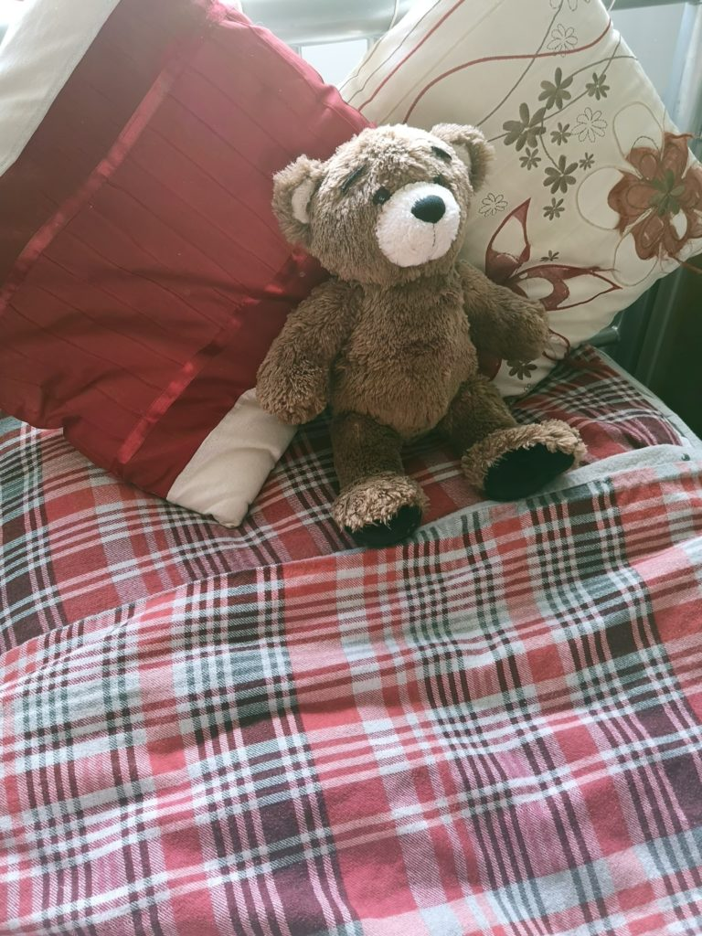 Cosy, red tartan bedding, two cushions in red, orange and cream, and a brown teddy bear.
