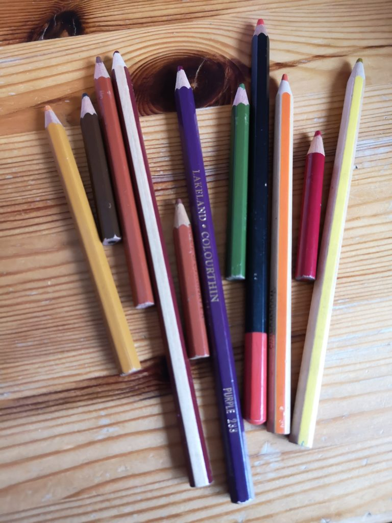 A selection of coloured pencils in autumnal colours, laid out on my desk