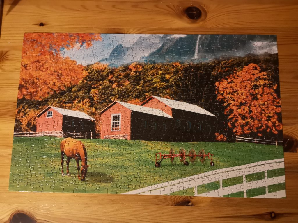 A completed jigsaw of an equestrian scene with a horse in a paddock, surrounded by trees with orange leaves.