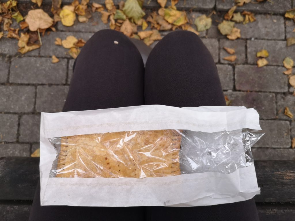 A pasty in a paper back resting on my legs. I am wearing black leggings. There are grey paving stones strewn with brown leaves in the background.