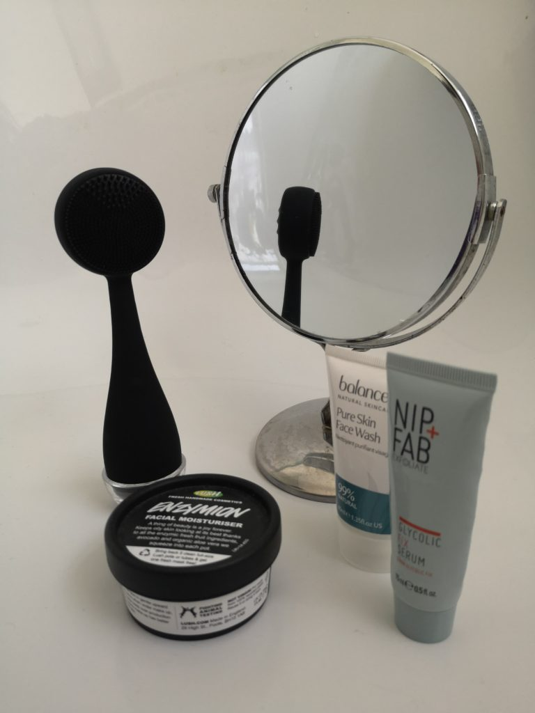 A black PMD Clean next to a mirror and several skincare products.