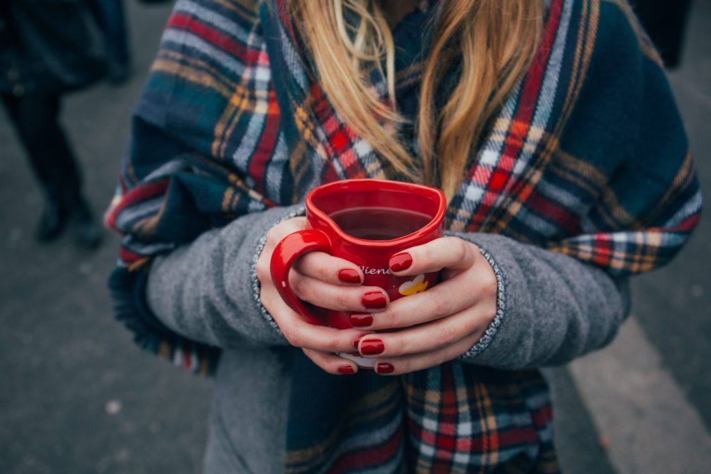 A woman wearing a tartan shawl over a grey jumper. Her nails are painted red and she is holding a red mug containing a hot drink.