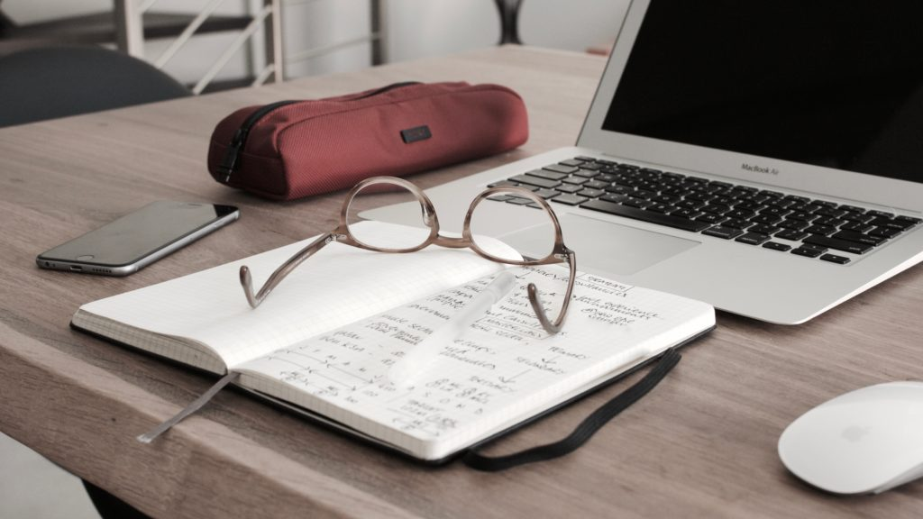 A desk with a notebook, laptop, pencil case, phone and pair of glasses on it.