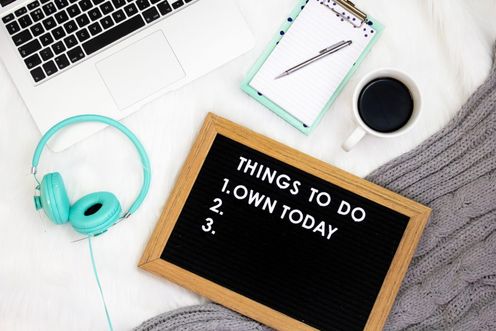 A slate with the quote: 'Things to Do - 1. Own Today 2. 3.' on it. There is a turquoise pair of headphones, a mug of coffee, a notebook and pen, a laptop and a grey scarf surrounding it.