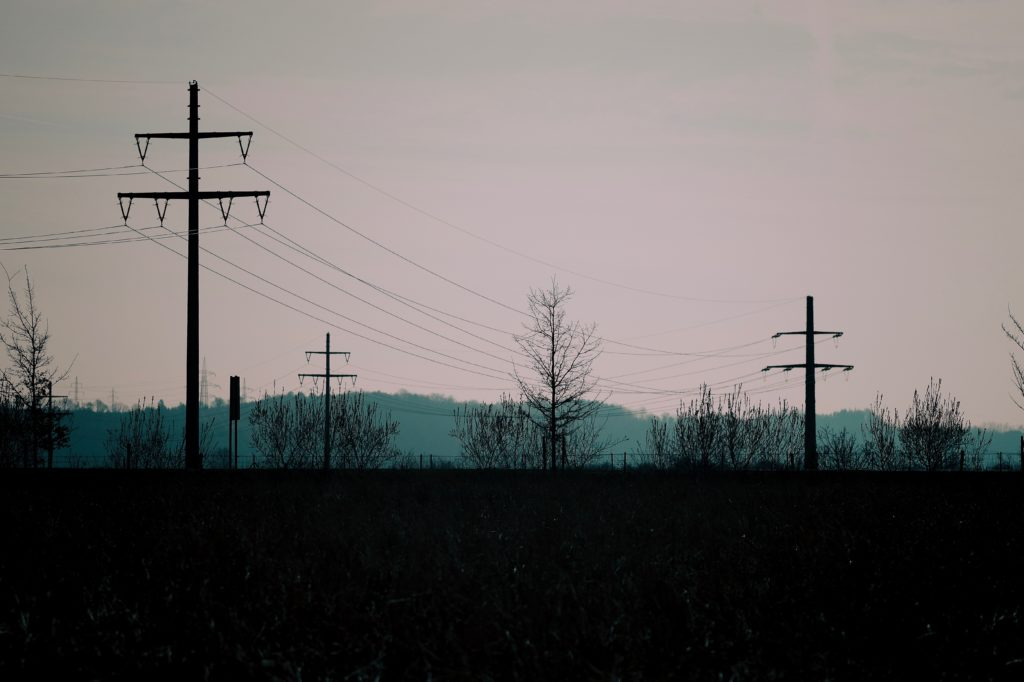Power lines and pilons against a grey sky.