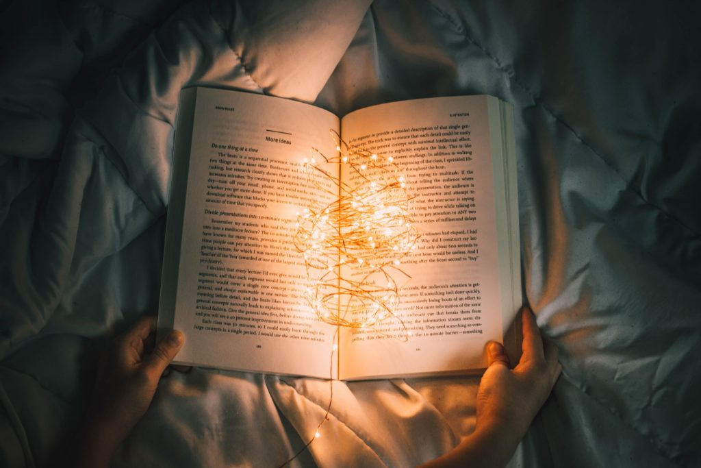 An open book with a string of fairy lights bundled in the middle, lighting the pages.