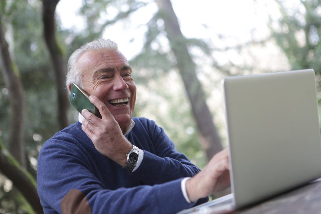 A man holding a phone to his ear whilst on his laptop. He is outdoors and smiling.
