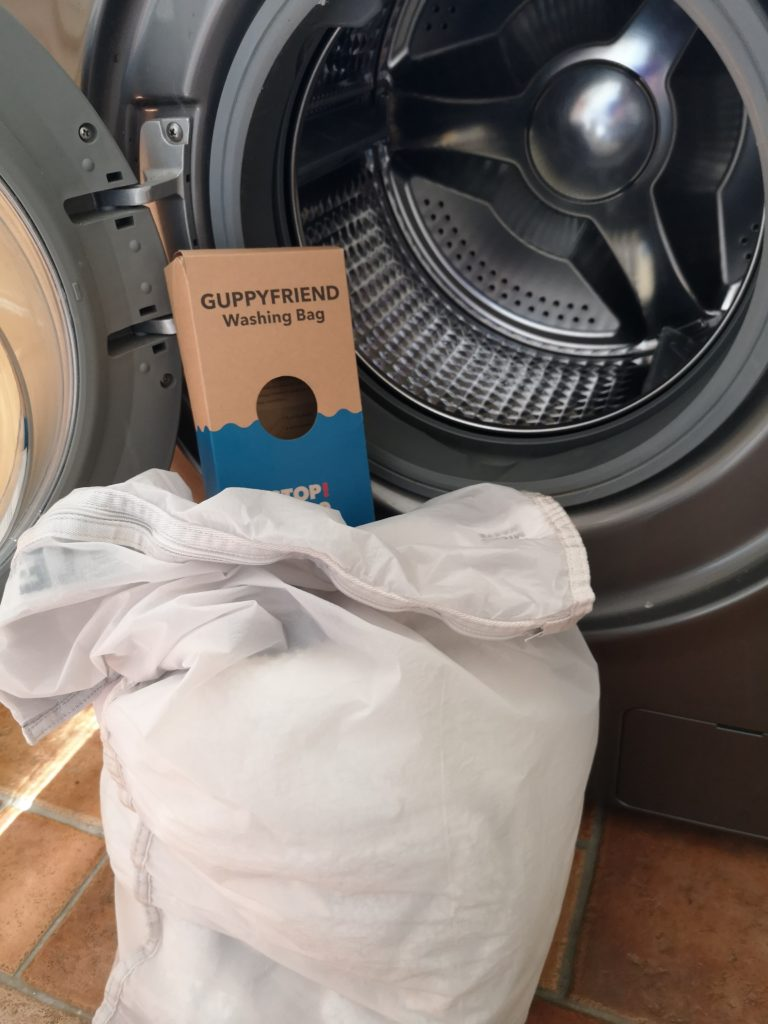 The Guppyfriend Washing Bag filled with clothes, propped up next to an open washing machine.
