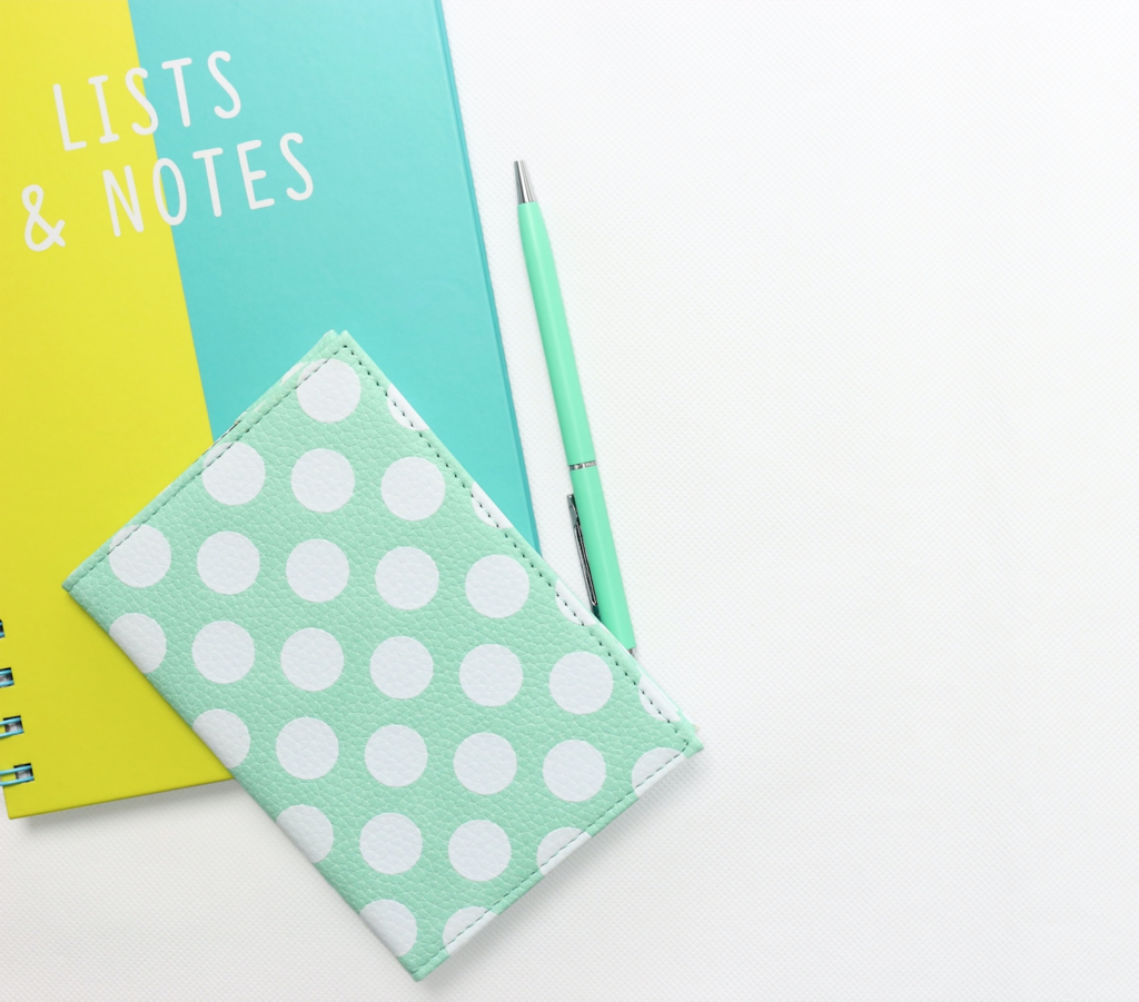 Two green and yellow notebooks and a turquoise pen against a white background.
