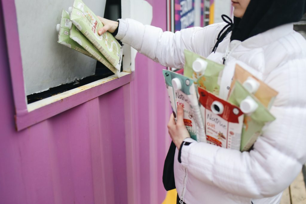 A woman putting Tetra Pak cartons into a pink recycling bin.