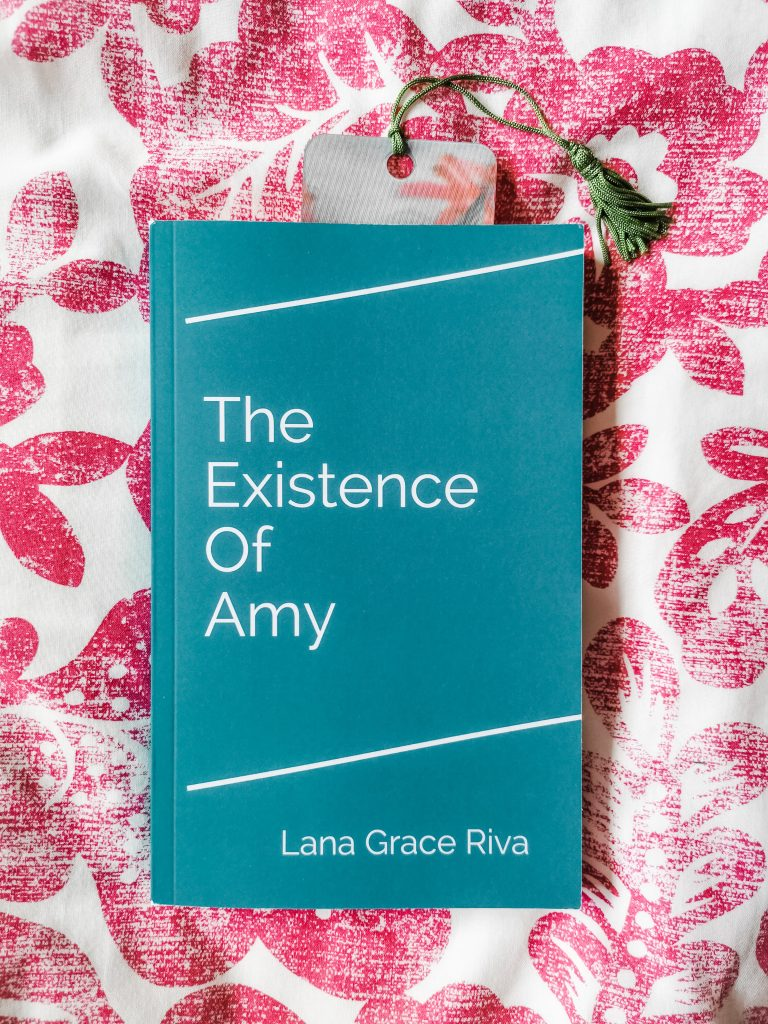 Paperback copy of The Existence of Amy by Lana Grace Riva