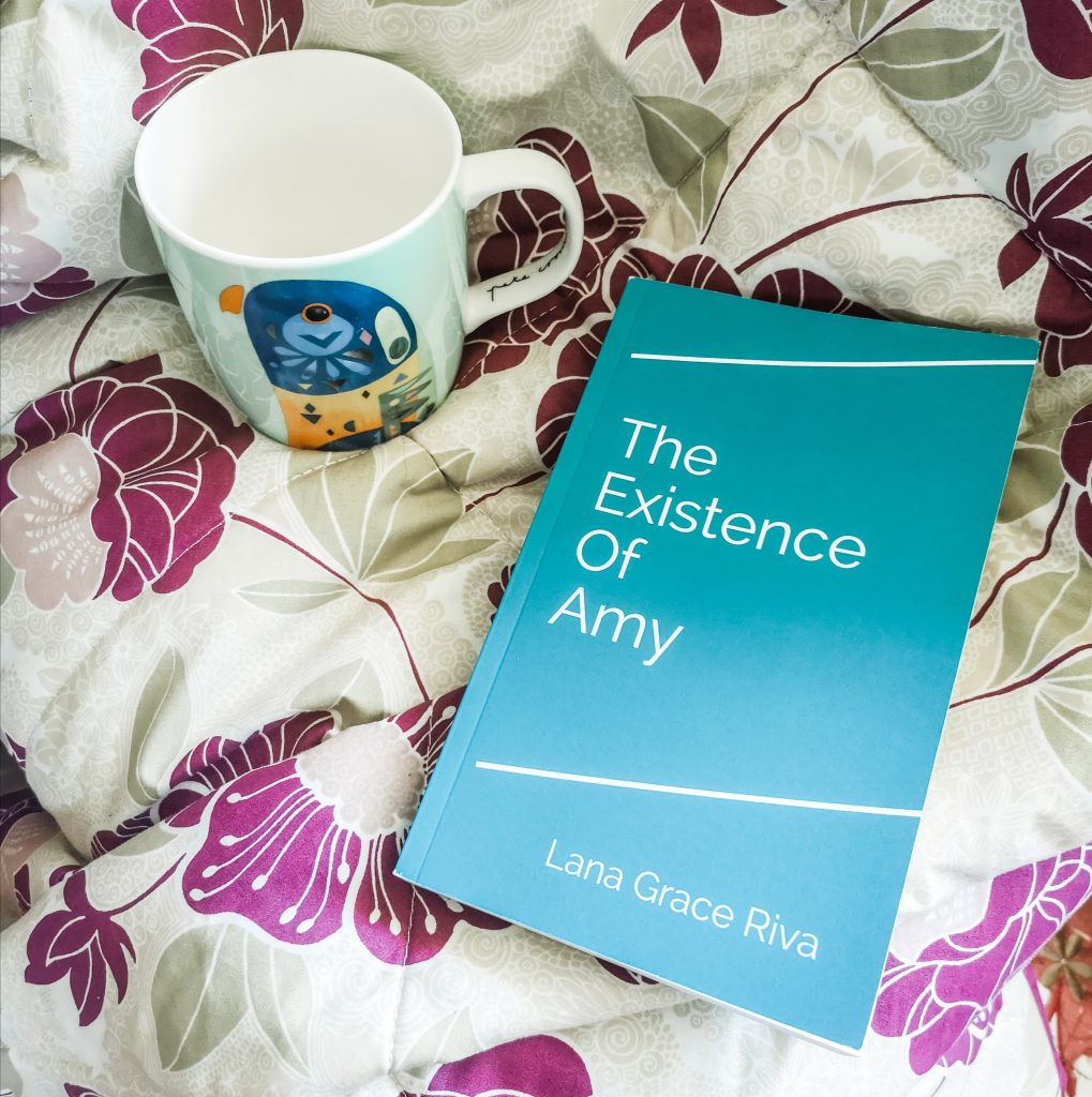 Paperback copy of The Existence Of Amy, laid on a flowery throw. A mug is placed next to it.