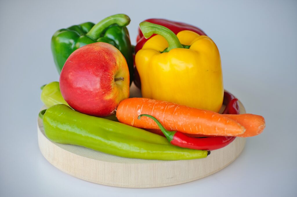 A platter of colourful bell peppers, chillis, apples and carrots