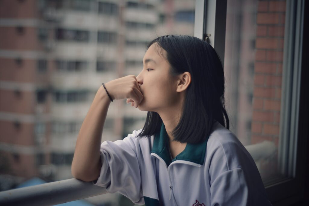 A woman staring out of a window with her hand on her chin, deep in thought