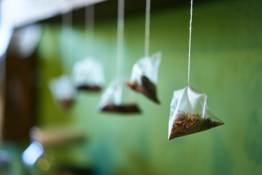 Herbal teabags hanging from their strings in front of a green background
