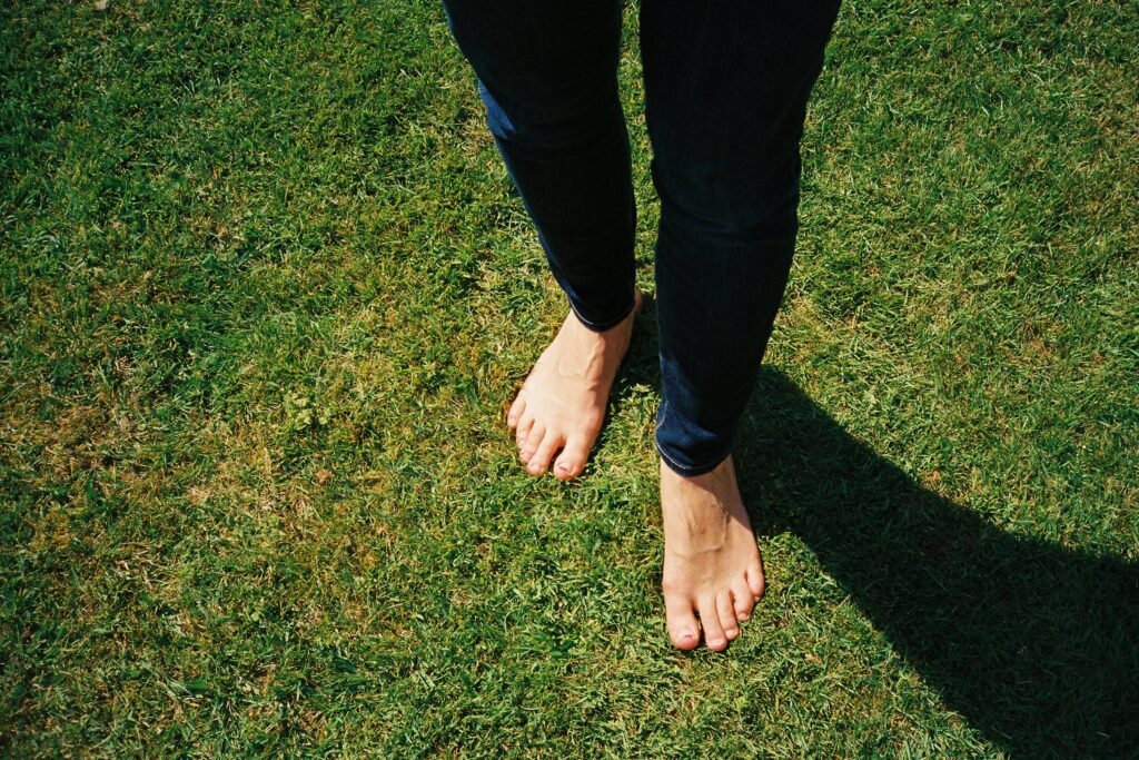 A pair of legs wearing jeans with bare feet on the grass outdoors