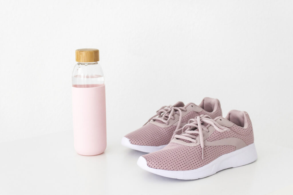 A pair of pink trainers and a pink water bottle against a white background.