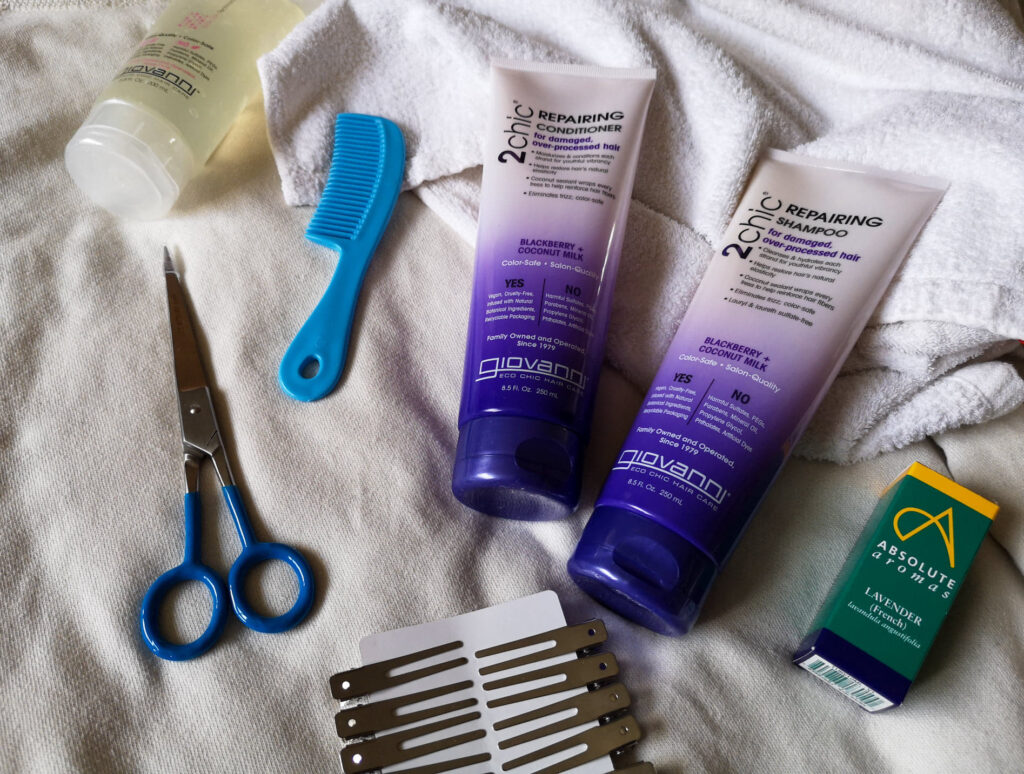 Various hair products laid out, including shampoo and conditioner, gel, a comb, hair cutting scissors, clips, a microfibre towel and lavender essential oil.