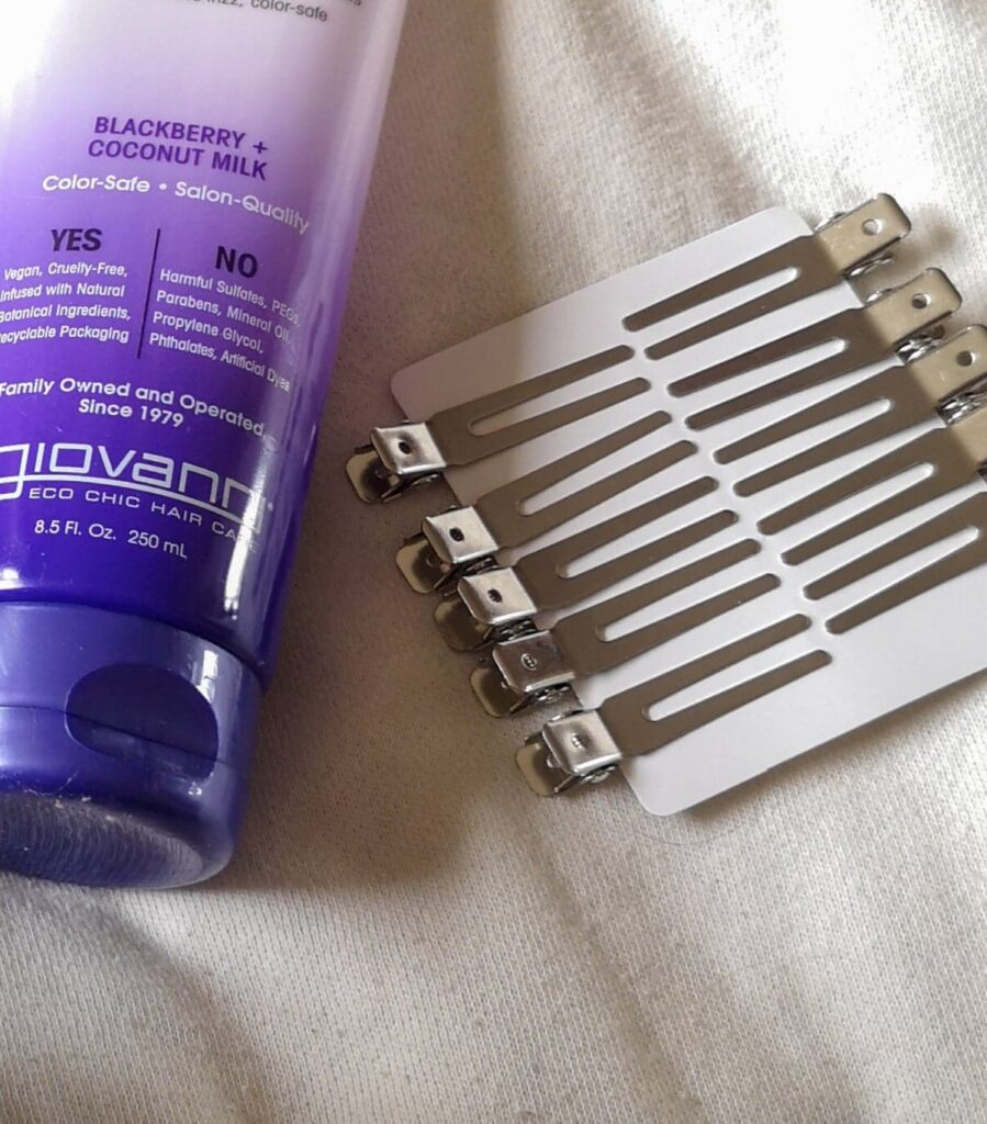 Silver coloured hair clips on a piece of card, next to a shampoo bottle.
