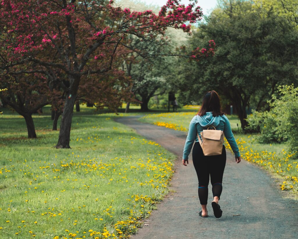A woman wearing a blue hoodie, black leggings and a cream rucksack, walking through a park. The grass is green with yellow flowers, and there are trees blooming with pink blossom.