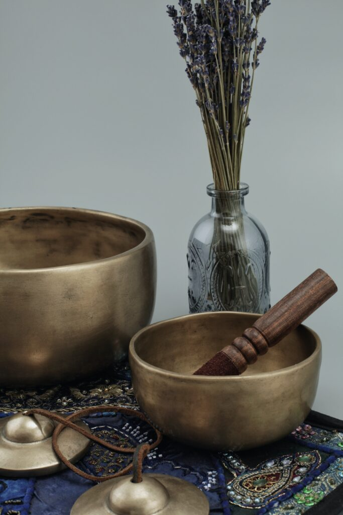 Two gold coloured Tibetan singing bowls, some Indian bells and a glass bottle of lavender stems on a blue, embroidered mat.