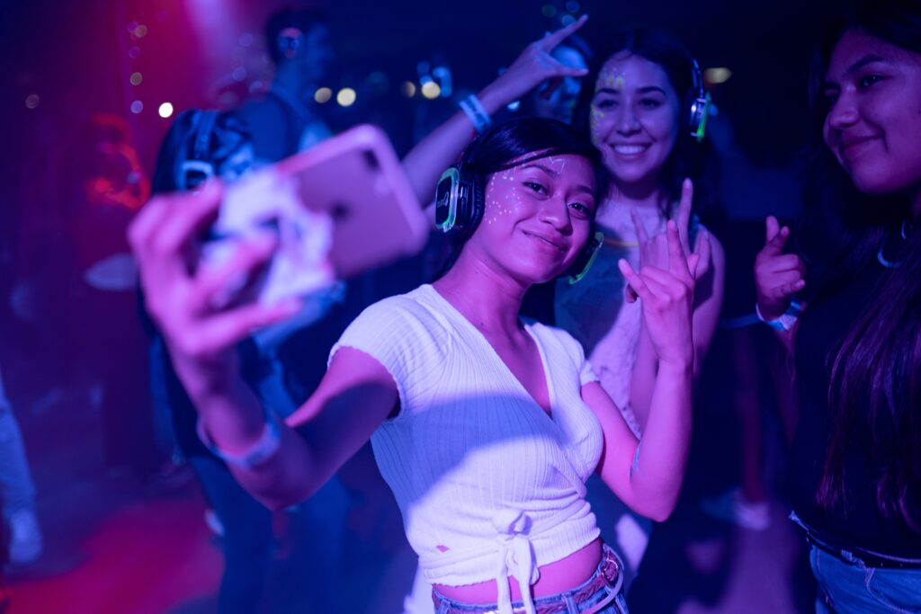 Three girls smiling and taking a selfie in a night club.