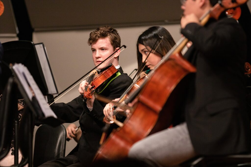 Students playing violin and cello in an orchestra.