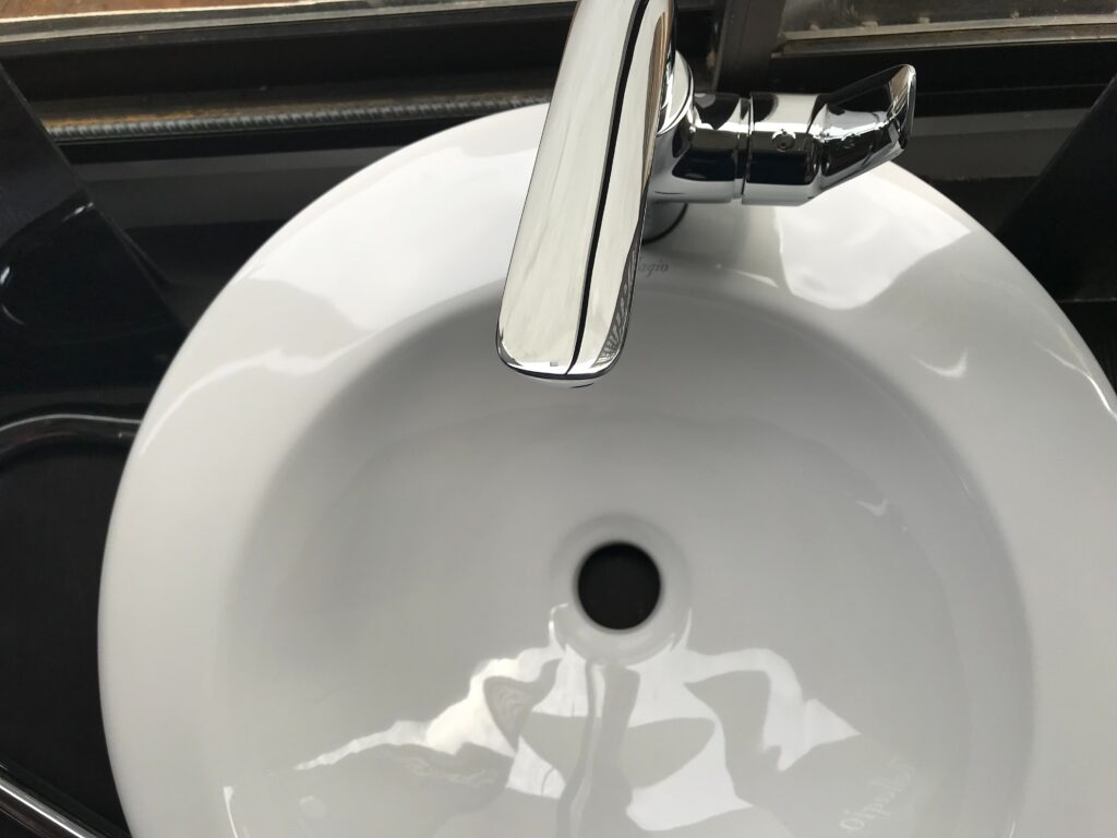 A close-up birds-eye view of a round, white sink with a silver coloured tap.