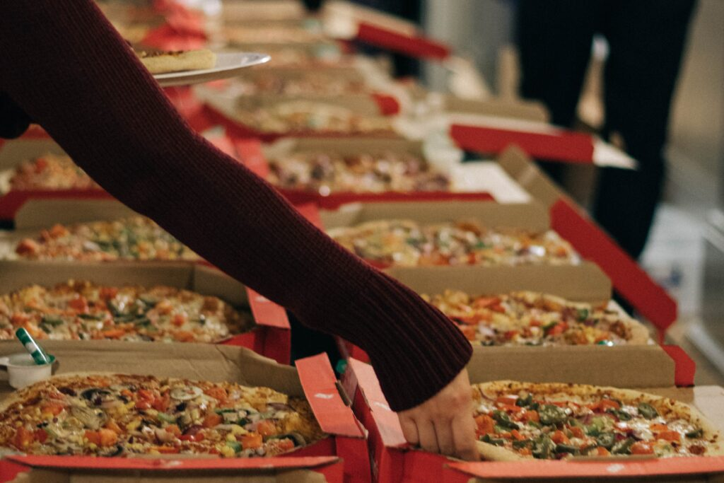 Dozens of takeaway pizzas laid out on a table. An arm is reaching over to grab a slice.