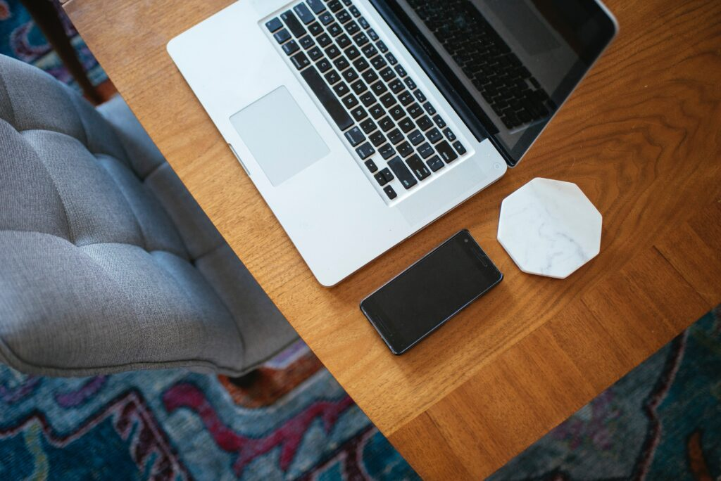 A silver Macbook on a brown wooden desk. There is a phone and white marble coaster next to it. A grey chair is tucked under the desk and there is a blue patterned carpet.